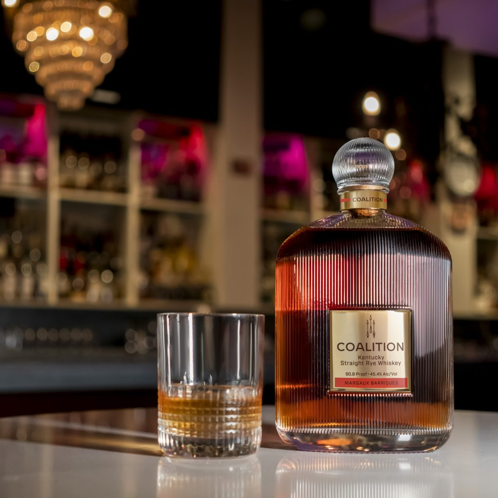Coalition Whiskey Mrgx with glass in bar